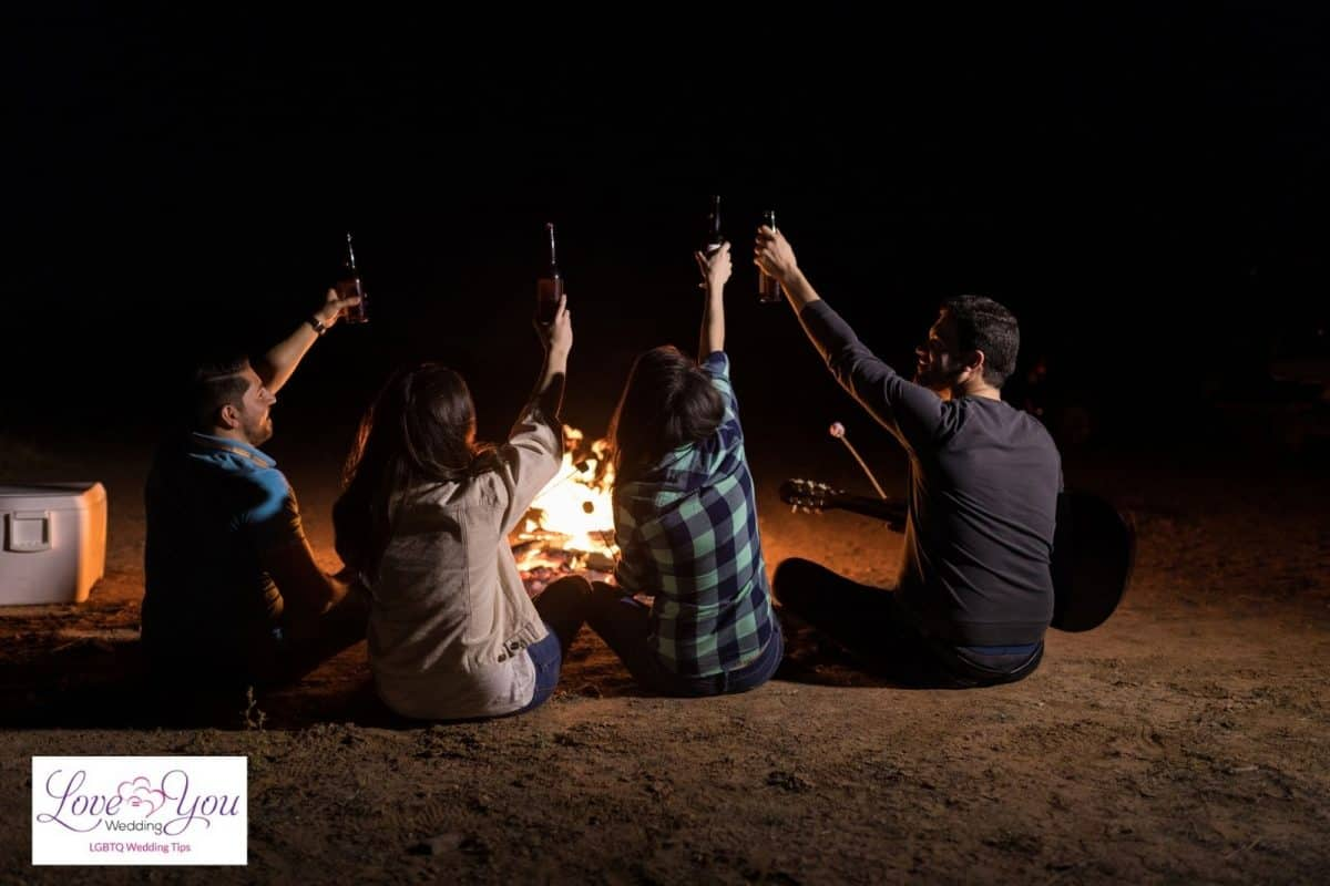 friends drinking beer and playing music in front of a bonfire
