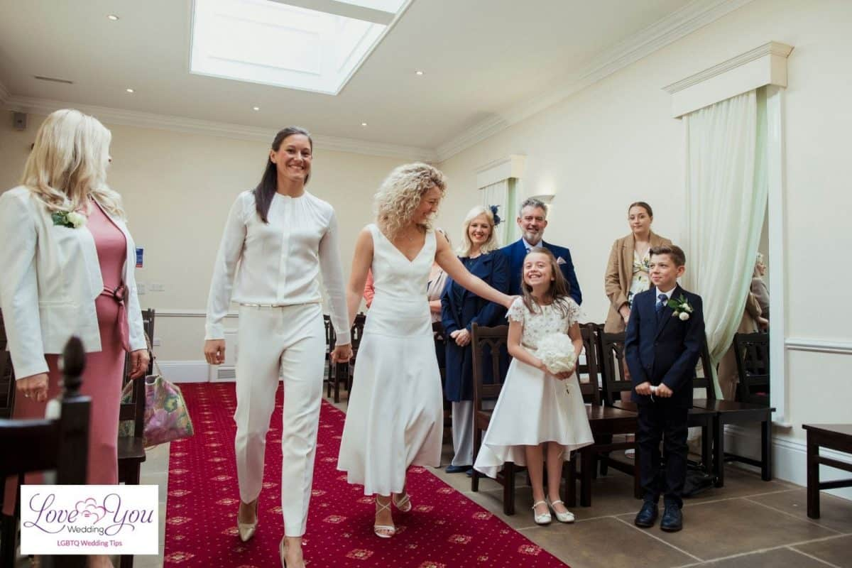 bride walking down the aisle with a lady and flower girl