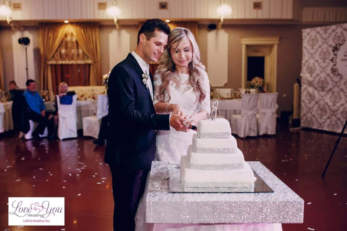bride and groom cutting their wedding cake while cake cutting songs are playing