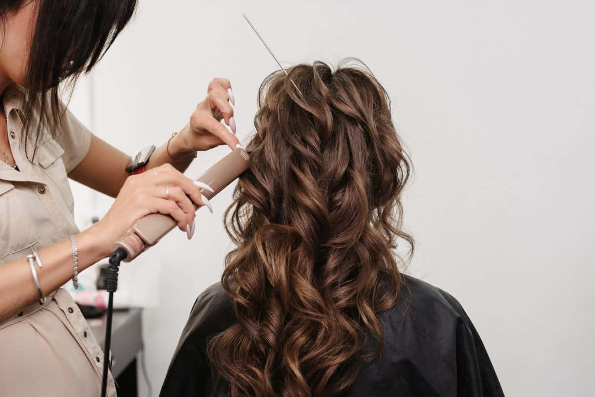hairdresser in a beauty salon makes a hairstyle for a girl bride with long curly brown hair