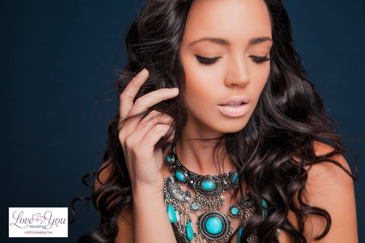 lady with curly hair and blue statement necklace