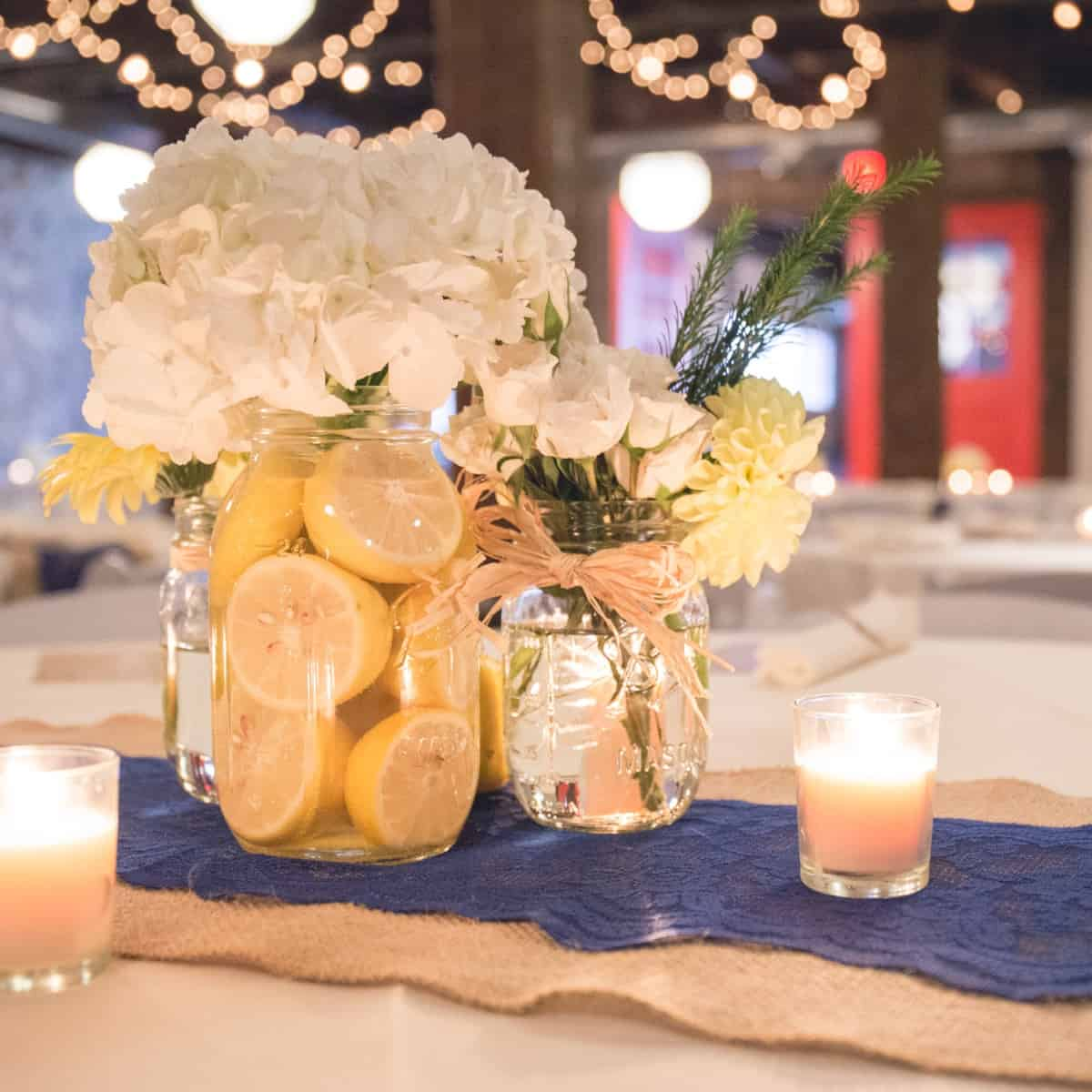 This portrait shows a wedding reception table centerpiece of white and yellow flowers in mason jars with lemons. Under the flowers is a burlap table runner with a blue lace table runner on top of it. There are small, lit candles surrounding the centerpiece. There are other tables and lights in the background.